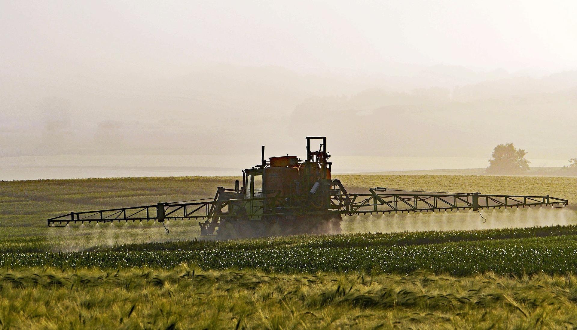 Champ dans lequel un tracteur épand des pesticides