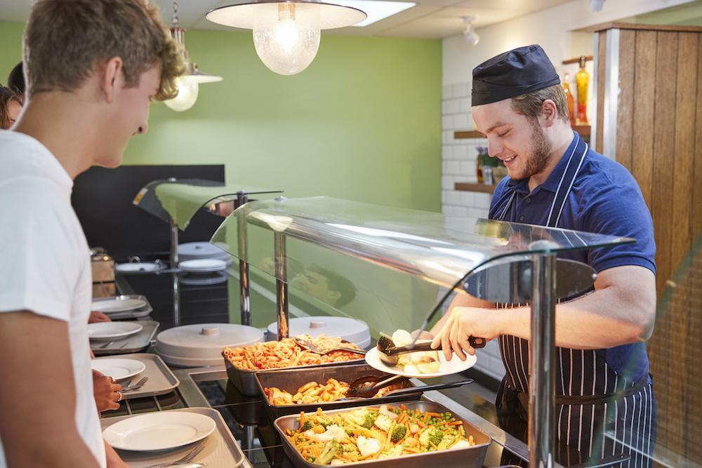 Restaurant collectif : serveur remplissant une assiette devant un étudiant
