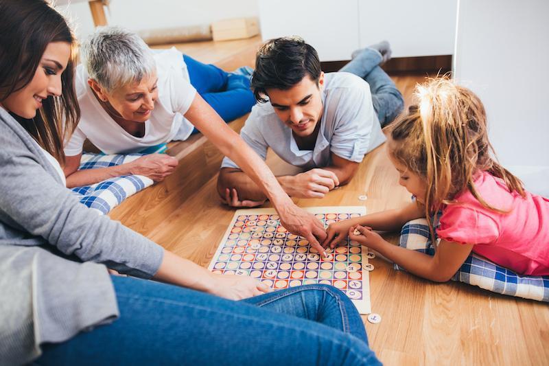 Une femme âgée, un couple hétérosexuel et une enfant jouent à un jeu de société