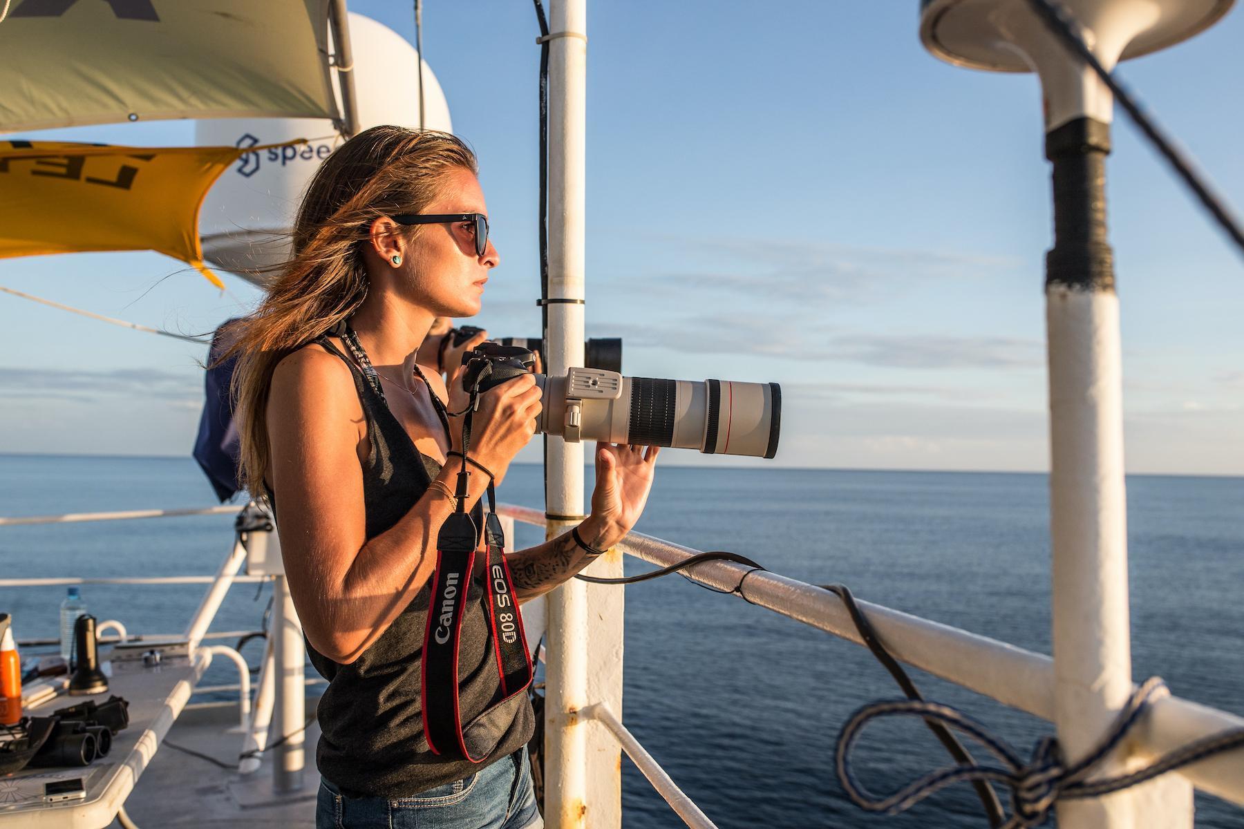 Margot, avec son appareil photo, sur un bateau, regardant l'horizon